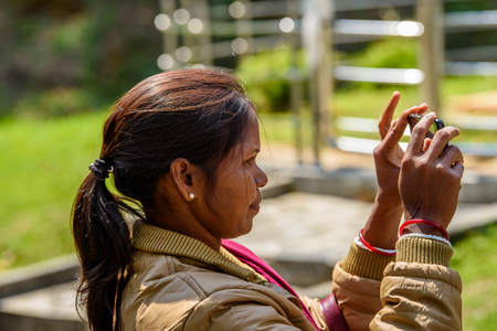 SIKKIM, INDIA - MAR 13, 2017: Unidentified Indian woman with pony tail wears an earing and mustard jacket tries to take a picture on her cellphone. Editorial