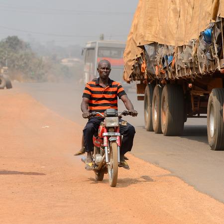 PIRA, BENIN - JAN 12, 2017: Unidentified Beninese man rides a motorcycle. Benin people suffer of poverty due to the bad economy.