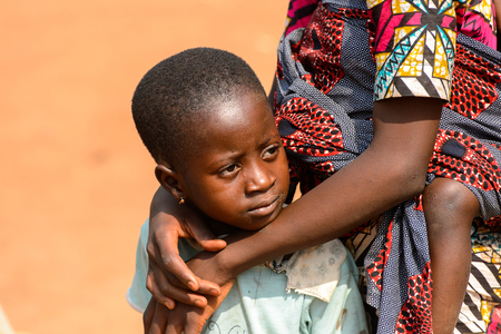BOHICON, BENIN - JAN 12, 2017: Unidentified Beninese little girl is hugged by her mother at the local market. Benin children suffer of poverty due to the bad economy. Editorial
