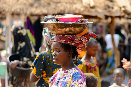 BOHICON, BENIN - JAN 12, 2017: Unidentified Beninese woman in national clothes carries a basin on her head at the local market. Benin people suffer of poverty due to the bad economy.