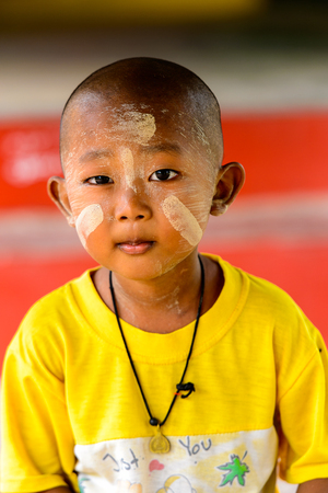 MONYWA, MYANMAR - AUG 27, 2016: Unidentified Burmese boy with a painted face. 68 per cent of Myanma people belong to Bamar ethnic group