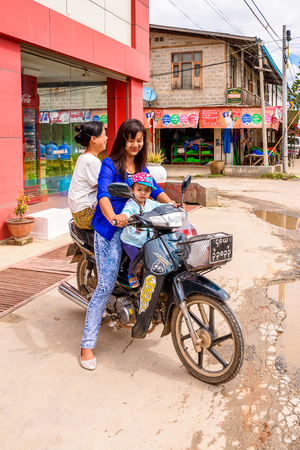 NYAUNGSHWE, MYANMAR - AUG 30, 2016: Unidentified Burmese girl withher child on a motorbike. 68 per cent of Myanma people belong to Bamar ethnic group