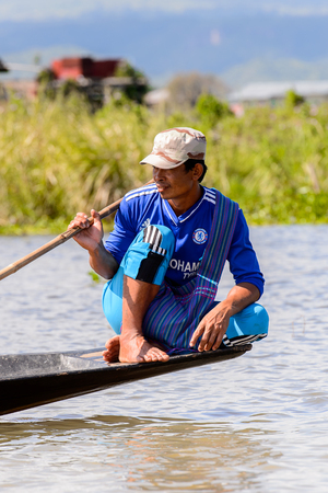 INLE LAKE, MYANMAR - AUG 30, 2016: Unidentified Burmese man in a wooden boat. 68 per cent of Myanma people belong to Bamar ethnic group Redactioneel