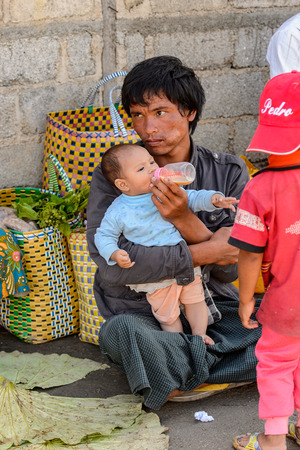 INLE LAKE, MYANMAR - AUG 30, 2016: Unidentified Burmese man with her little child. 68 per cent of Myanma people belong to Bamar ethnic group Redactioneel