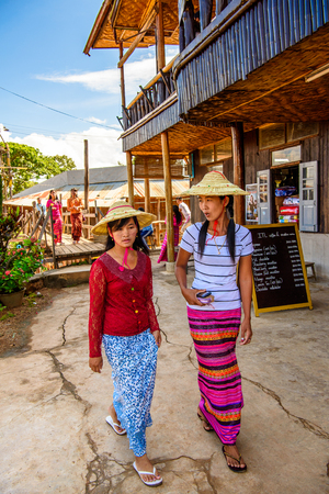 INLE LAKE, MYANMAR - AUG 30, 2016: Unidentified Burmese walk in the street. 68 per cent of Myanma people belong to Bamar ethnic group