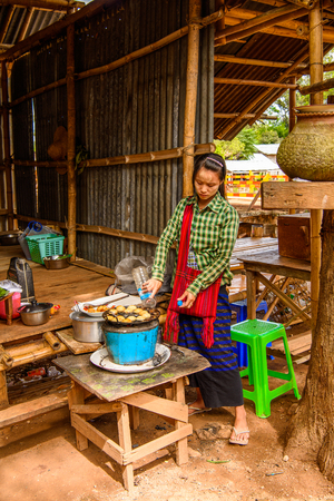 INLE LAKE, MYANMAR - AUG 30, 2016: Unidentified Burmese woman works  on a market place, Inle Lake. 68 per cent of Myanma people belong to Bamar ethnic group Redactioneel