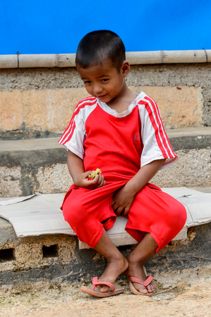INLE LAKE, MYANMAR - AUG 30, 2016: Unidentified Burmese little gitl in a red shirt. 68 per cent of Myanma people belong to Bamar ethnic group
