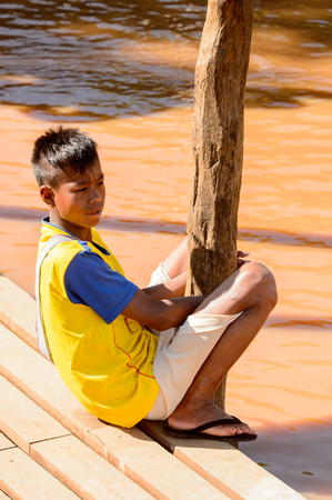 INLE LAKE, MYANMAR - AUG 30, 2016: Unidentified Burmese boy sits on a pier. 68 per cent of Myanma people belong to Bamar ethnic group