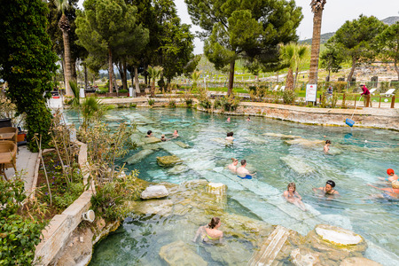 PAMUKKALE, TURKEY - APR 18, 2015: Unidentified tourists swim in the Antique pool (Cleopatra's Bath) in Pamukkale. It's a popular touristic destination during a Pamukkale visit