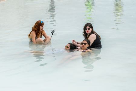 PAMUKKALE, TURKEY - APR 18, 2015: Unidentified girls swim in the hot spring on the travertines of Pamukkale, Turkey. It's a UNESCO World Heritage site Editorial