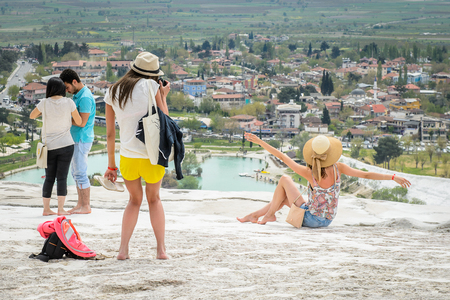 PAMUKKALE, TURKEY - APR 18, 2015: Unidentified girl makes pictures on the travertines of Pamukkale, Turkey. It's a UNESCO World Heritage site Editorial