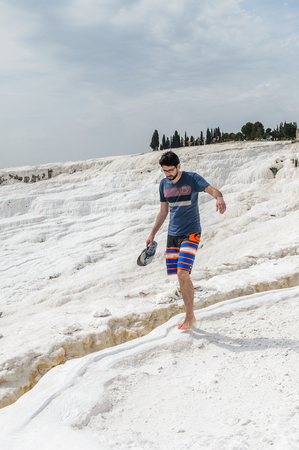 PAMUKKALE, TURKEY - APR 18, 2015: Unidentified tourist walks down on the travertines of Pamukkale, Turkey. It's a UNESCO World Heritage site
