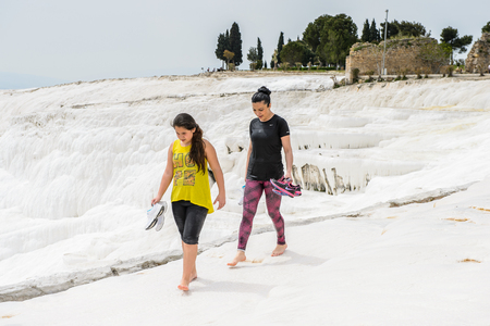 PAMUKKALE, TURKEY - APR 18, 2015: Unidentified tourists on the travertines of Pamukkale, Turkey. It's a UNESCO World Heritage site Editorial