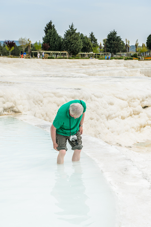 PAMUKKALE, TURKEY - APR 18, 2015: Unidentified tourist man with a camera on the travertines of Pamukkale, Turkey. It's a UNESCO World Heritage site Editorial