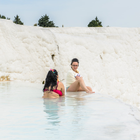 PAMUKKALE, TURKEY - APR 18, 2015: Unidentified girls in a hot spring on the travertines of Pamukkale, Turkey. It's a UNESCO World Heritage site