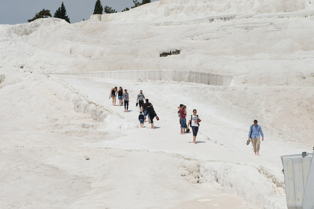 PAMUKKALE, TURKEY - APR 18, 2015: Unidentified tourists walk on the travertines of Pamukkale, Turkey. It's a UNESCO World Heritage site Editorial