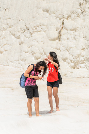 PAMUKKALE, TURKEY - APR 18, 2015: Unidentified friend on the travertines of Pamukkale, Turkey. It's a UNESCO World Heritage site