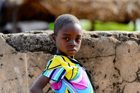 KOUTAMMAKOU, TOGO - JAN 13, 2017: Unidentified Togolese little girl in colored shirt stands near the well in the village. Togo children suffer of poverty due to the bad economy.