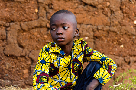 MASSIF KABYE, TOGO - JAN 13, 2017: Unidentified Togolese  little boy in colored shirt squats in the village. Togo children suffer of poverty due to the bad economy.