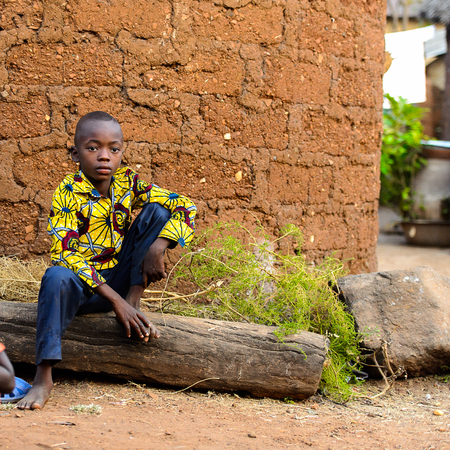 MASSIF KABYE, TOGO - JAN 13, 2017: Unidentified Togolese  little boy in colored shirt sits in the village. Togo children suffer of poverty due to the bad economy. Editorial