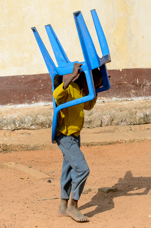 KARA REG., TOGO - JAN 14, 2017: Unidentified Konkomba little boy carries a blue plastic chair in the village. Konkombas are ethnic group of Togo