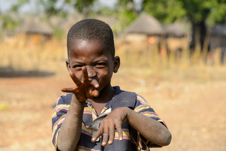 GHANI, GHANA - JAN 14, 2017: Unidentified Ghanaian boy looks ahead and raises his hand in the Ghani village. Ghana children suffer of poverty due to the bad economy. Editorial