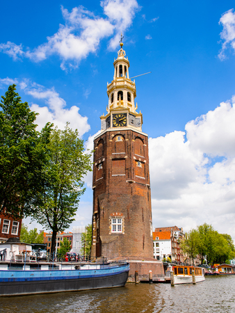 AMSTERDAM, NETHERLANDS - JUN 1, 2015: Amsterdam clock tower. Amsterdam is the capital city and most populous city of the Kingdom of the Netherlands