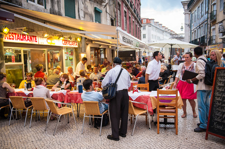LISBON, PORTUGAL - JUN 20, 2014: Unidentified tourists walk and eat in the touristic area in Lisbon, Portugal. Lisbon is the westernmost large city Europe and the seventh-most-visited city in Southern Europe