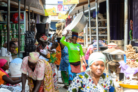 KUMASI, GHANA - JAN 15, 2017: Unidentified Ghanaian woman in green shirt carries a basin on her head at the Kumasi market. Ghana people suffer of poverty due to the bad economy.