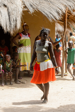 ORANGO ISL., GUINEA BISSAU - MAY 3, 2017: Unidentified local The girl dances near the clay house  during Vaca Bruto, traditional Mask dance