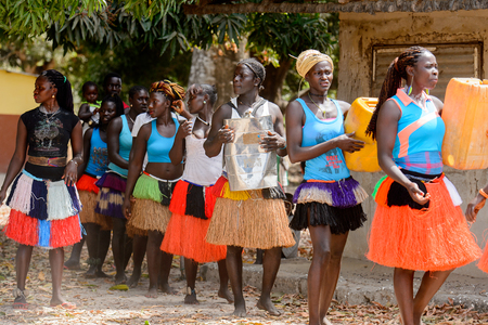 ORANGO ISL., GUINEA BISSAU - MAY 3, 2017: Unidentified local Women dance and hold canisters during Vaca Bruto, traditional Mask dance