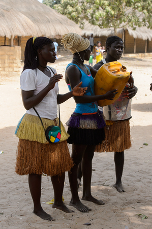 ORANGO ISL., GUINEA BISSAU - MAY 3, 2017: Unidentified local A women dance and hold a canisters during Vaca Bruto, traditional Mask dance
