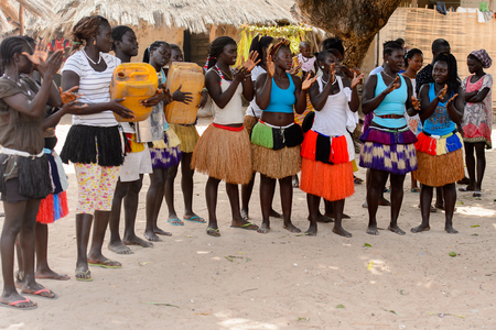 ORANGO ISL., GUINEA BISSAU - MAY 3, 2017: Unidentified local Women in straw skirts clap their hands and knock on cans  during Vaca Bruto, traditional Mask dance