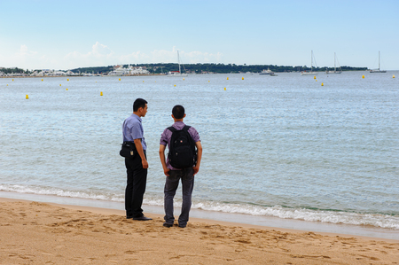 CANNES, FRANCE - JUNE 25, 2014: Unidentified tourists on the beach of  Cote d'Azur, Cannes. Cannes hosts the annual Cannes Film festival from 1949