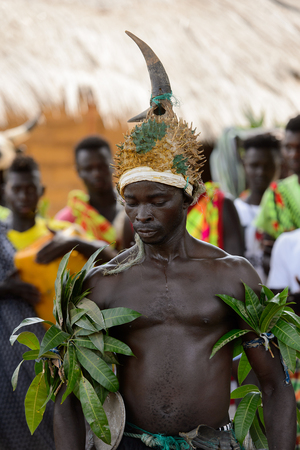 ORANGO ISL., GUINEA BISSAU - MAY 3, 2017: Unidentified local A man in a hat with horns dances  during Vaca Bruto, traditional Mask dance