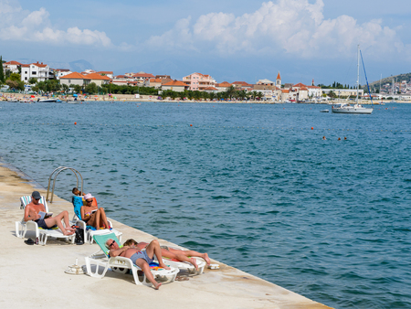 DALMATIA, REGION OF SPLIT, CROATIA - AUG 20, 2014: Beach of the Adriatic coast. Coast of the Adriatic Sea in Dalmatia became a popular destination for millions of tourists
