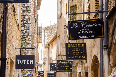 SAINT-PAUL-DE-VENCE, FRANCE - JUN 25, 2014: Signs with names of galleries or restaurants of Saint Paul de Vence, one of the oldest towns of the Frence Riviera. Town of painters and galleries