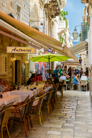 DUBROVNIK, CROATIA - AUG 21, 2014: Unidentified tourists in a Small restaurant of the Old town of Dubrovnik, Croatia. Dubrovnik is a UNESCO World Heritage site
