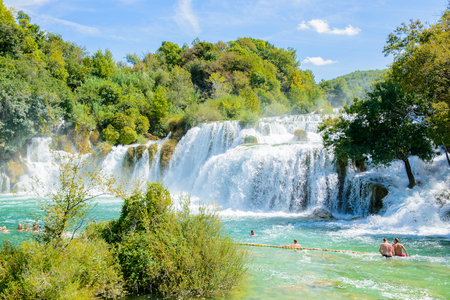 KRKA NATIONAL PARK, CROATIA - AUG 26, 2014: Unidentified tourist swim in the Krka River in the Krka National Park in Croatia. It is one of the National Parks in Croatia with an area of 109 square kilometers