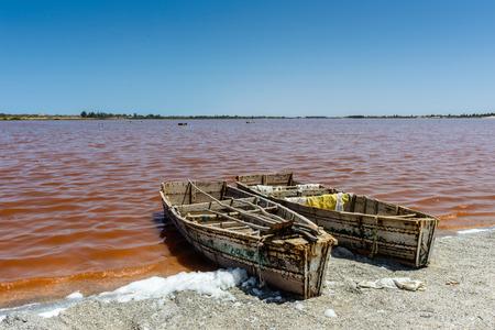 Barco de marinero sobre el lago de agua rosa en Senegal, África Foto de archivo