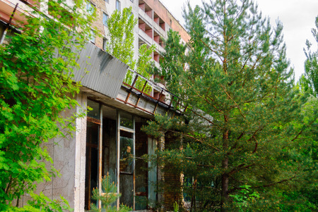 Abandoned house and green trees growing just in the street in Pripyat, a ghost town in northern Ukraine, evacuated the day after the Chernobyl disaster on April 26, 1986