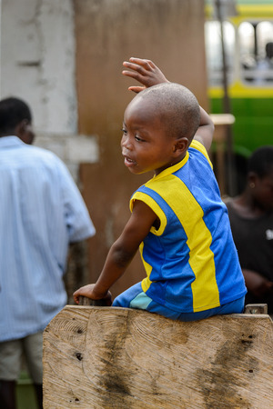 ACCRA, GHANA - JAN 8, 2017: Unidentified Ghanaian little boy in yellow and blue shirt. Children of Ghana suffer of poverty due to the economic situation