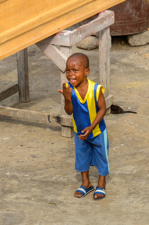 ACCRA, GHANA - JAN 8, 2017: Unidentified Ghanaian little boy in blue and yellow suit shows his fingers. Children of Ghana suffer of poverty due to the economic situation