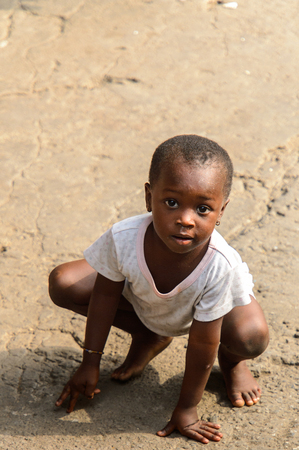 ACCRA, GHANA - JAN 8, 2017: Unidentified Ghanaian little girl in dirty white dress squats on the street. Children of Ghana suffer of poverty due to the economic situation