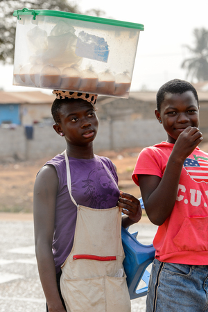 ACCRA, GHANA - JAN 8, 2017: Unidentified Ghanaian girl in purple shirt carries a basin on her head and her friend. People of Ghana suffer of poverty due to the economic situation