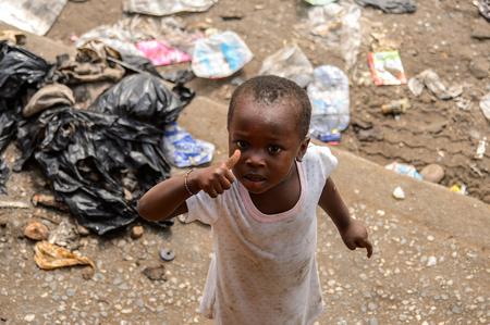 ACCRA, GHANA - 8 DE ENERO DE 2017: Niña ghanesa no identificada con vestido blanco muestra su dedo. Los niños de Ghana sufren de pobreza debido a la situación económica