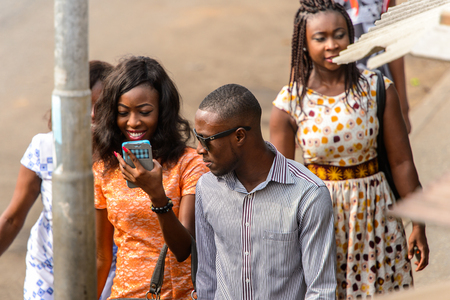 ACCRA, GHANA - JAN 8, 2017: Unidentified Ghanaian man in sunglasses and shirt walks on the street with a woman who holds a cellphone. People of Ghana suffer of poverty due to the economic situation Stock Photo - 112565541