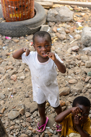 ACCRA, GHANA - JAN 8, 2017: Unidentified Ghanaian little girl in dirty white dress plays in the trash. Children of Ghana suffer of poverty due to the economic situation Editoriali