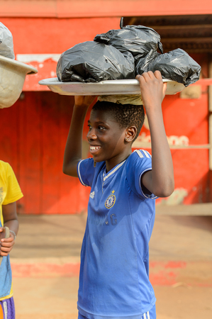 ACCRA, GHANA - JAN 8, 2017: Unidentified Ghanaian boy carries the basin on his head. Children of Ghana suffer of poverty due to the economic situation