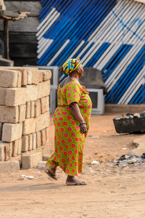 ACCRA, GHANA - JAN 8, 2017: Unidentified Ghanaian woman in colored dress and headscarf walks on the street. People of Ghana suffer of poverty due to the economic situation